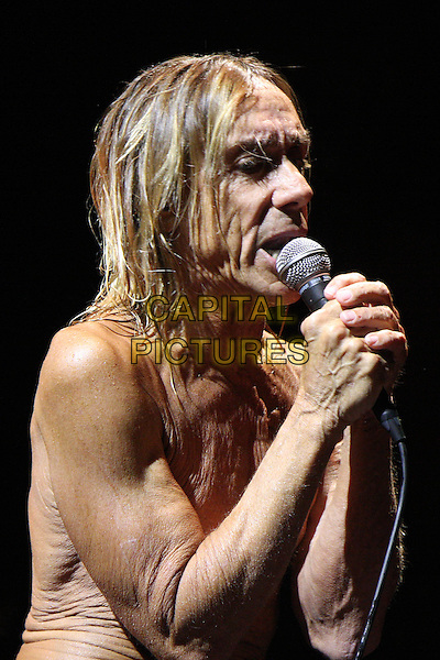IGGY AND THE STOOGES (Iggy Pop (born James Newell Osterberg)).Performing live at the Hammersmith Apollo, London, England..May 2nd, 2010.stage concert live gig performance music half length chest wrinkled skin singing funny microphone .CAP/MAR.© Martin Harris/Capital Pictures.