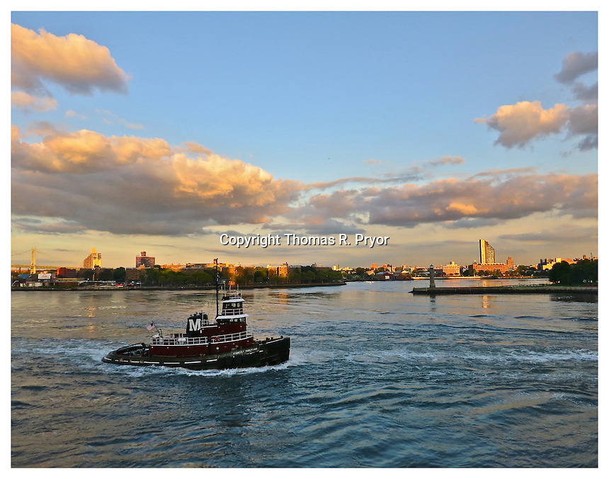 YORKVILLE, NY - SEPTEMBER 5: Photograph of tugboat passing Roosevelt Island Lighthouse on the East River from Carl Schurz Park taken in Yorkville, New York on September 5, 2012. Photo Credit: Thomas R. Pryor