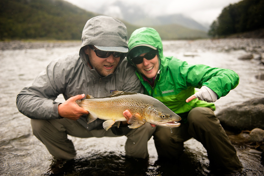 A pair of anglers celebrate landing a brown trout in the Southern Alps of New Zealand.