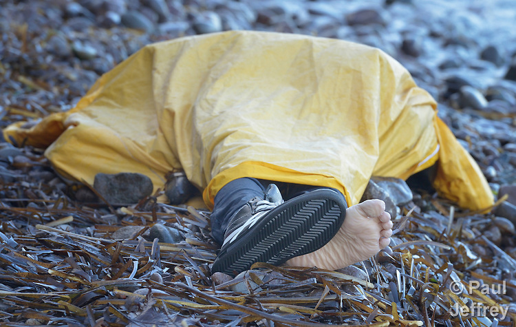 The body of a refugee child lies on a beach on the Greek island of Lesbos on November 1, 2015. It was covered with a plastic raincoat by Spanish lifeguards until it could be picked up by local authorities. The body appeared to be that of an Afghan boy of about 8 years of age. Thousands of refugees have died this year attempting to cross the Aegean from Turkey to Greece. Fleeing violence in Syria, Iraq, Afghanistan and elsewhere, most are on their way toward western Europe.