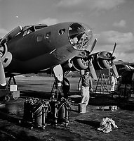 Lubricating and servicing a new B-17F <br /> Flying Fortress bomber for flight tests at the airfield of Boeing's Seattle plant, 1942.<br /> <br /> Photo by Andreas Feininger.