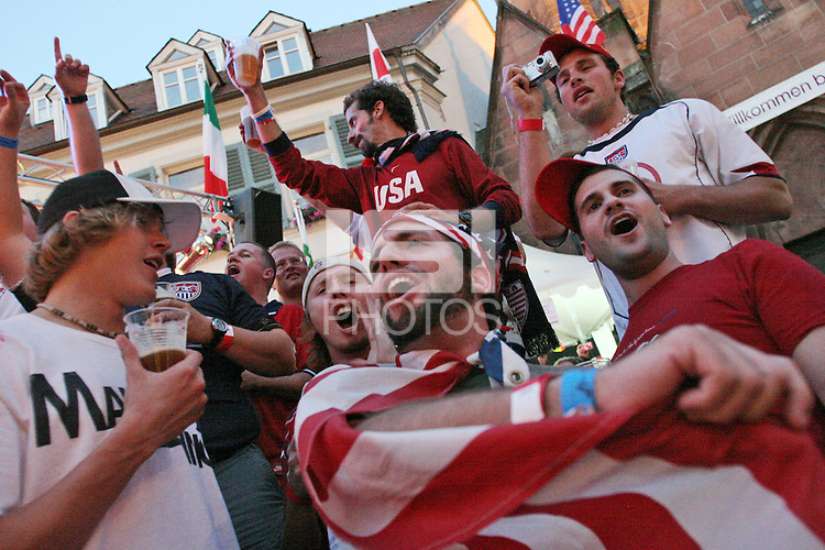USA National Soccer Team fans join together with Italian fans and other locals to party, cheer,  wave flags and sing together near an outdoor music stage in the old town of Kaiserslautern Germany  on Saturday June 17th, 2006 in Kaiserslautern, Germany. The United States fans had gathered for an organized rally in the old town at the Brauhaus Market pub next door and ventured outside to join the party on the streets of the old town during half-time of the Mexico-Angola game.