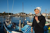 Japan, Mie Prefecture, Osatsu, Toba City. Women Ama free divers. Once pearl divers, they now collect seaweed, conch, lobster, shellfish. Approaching the beach for their dive, they wear white hoods for good luck, symbolic of the Ama divers. Model released