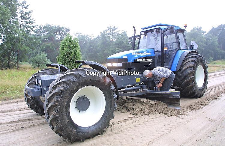 Foto: VidiPhoto..'t HARDE - Met een voor Nederland nieuwe tractor (New Holland TM 115) worden op de schietterreien van defensie in  't Harde de zandwegen geegaliseerd. De tot 7 meter verlengde tractor is zowel aan de onderzijde als aan de bovenzijde bepantserd en heeft aan de voorzijde pantserglas van 3,5 cm. dik. De zes cilinder motor heeft een vermogen van 120 pk. De schakeling werkt via een joystick. De bepantsering is nodig als bescherming tegen niet-ontplofte munitie. Foto: Eigenaar Evert Schuiteman uit Elspeet controleert de systemen. (06-51828256)