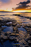 Sunset along a rocky shoreline on Maui.