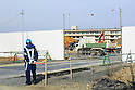 A worker patrols the entrance of a construction in front of the abandoned Kesennuma Koyo High School, five years after the 2011 Tohoku Earthquake and Tsunami on February 9, 2016 in Miyagi Prefecture, Japan. Over 1000 residents of the fishing town lost their lives in the disaster and although some rebuilding has taken place there is still much work to do to rehouse people still living in some 2000 temporary homes and to clear all of the rubble. (Photo by Rodrigo Reyes Marin/AFLO)