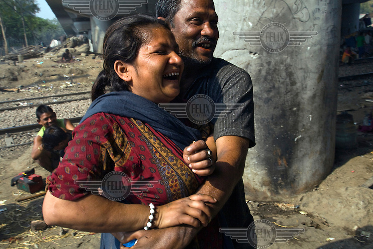 Monu and Seema flirt and play on a piece of waste ground beneath a flyover near Okhla station. .