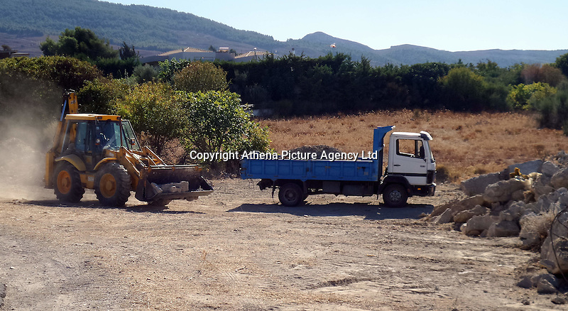 Pictured: A digger loads soil to a tipper lorry from the new site to be taken to the farmhouse in order to be searched in Kos, Greece. Sunday 09 October 2016<br />Re: Police teams led by South Yorkshire Police are searching for missing toddler Ben Needham on the Greek island of Kos.<br />Ben, from Sheffield, was 21 months old when he disappeared on 24 July 1991 during a family holiday.<br />Digging has begun at a new site after a fresh line of inquiry suggested he could have been crushed by a digger.