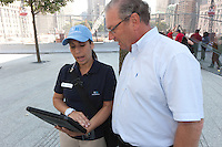 A guide at the National 9/11 Memorial in New York City uses an iPad to provide directions to a visitor.