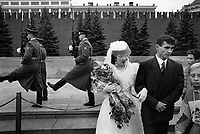 Russia. Moscow. A newly married couple stands on the Red Square. The bride wears a white wedding dress, a hat and a veil. She holds a bouquet of flowers and the groom's arm. In their back, a group of soldiers, all presidential guards, are marching and changing shifts at Lenin mausoleum. The Red Square is a city square and is often considered the central square of Moscow. View on the Kremlin and its protective walls. Moscow is the capital city and the most populous federal subject of Russia. © 1993 Didier Ruef