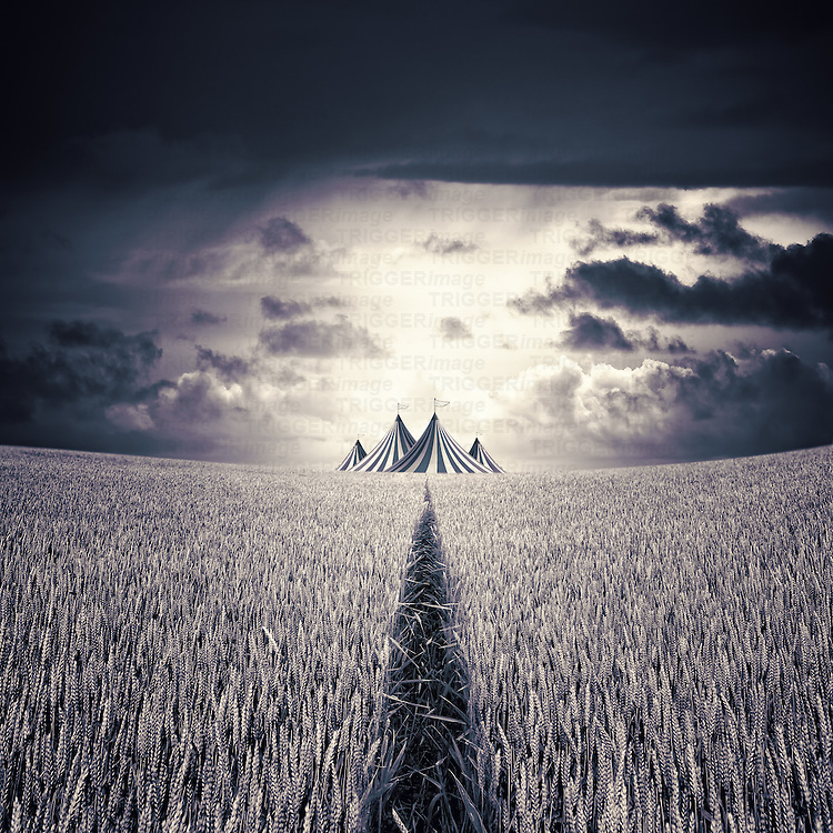 A circus tent with flags in a corn field under dark skies with sunlight and clouds