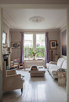 Painted floorboards reflect light up into the living room, its antique furnishings inspired by period French interiors