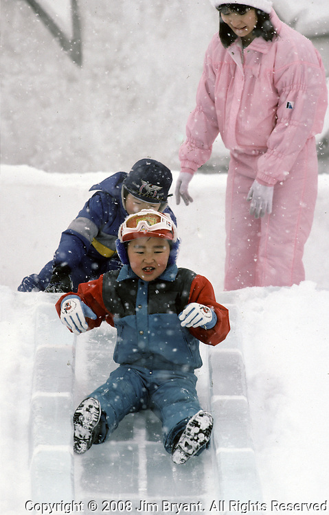 Festival goers slide down an ice slide at the Japanese Self Defense Force Base at Makomanai. Nearly two million visitors pour into Sapporo every February to see over 200 ice and snow sculptures. These are not traditional Frosty the Snowmen, but huge carved and chiseled Samurai Warriors, Buddhists gods, historical heroes of fairy tales and Walt Disney characters. Some stand as big as buildings. Chiseled out of tons of packed snow, the sculptures are the pride and job of the residents of Sapporo, Japan, who hosts the world famous Ice and Snow Sculpture Festival for five days in early February.Themes of the sculptures are picked from Kabuki stages, historical characters or fairy tales. (Jim Bryant Photo).....