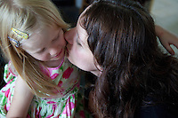 Polish mother kissing sad daughter age 32 and 4. Zawady Central Poland
