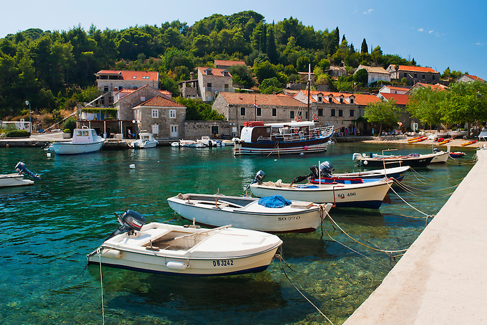 Photo of boats in the port, Sipan Island (Sipano), Elaphiti Islands, Dalmatian Coast, Croatia. This photo shows boats in the port at Sipan Island in the Elaphiti Islands. The Elaphiti Islands are a small archipelago situated just a short boat crossing from Dubrovnik on the Dalmatian Coast of Croatia. For their quiet, rustic villages, quaint cathedrals and the inviting, blue, crystal clear Adriatic Sea, visiting Sipan (Sipano), Kolocep (Kalamota) and Lopud Island,  the three main islands in the Elaphiti Islands makes for a fantastic day trip from Dubrovnik. Sipan (Sipano) is the largest of the Elaphiti Islands being home to c450 people. Arriving into one of the two ports, filled with fishing boats and sailing boats, Sipan (Sipano) has the captivating feel of a typical, quiet Croatian island.