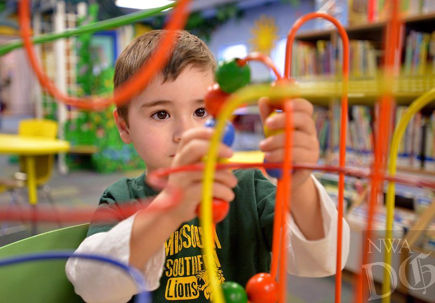 STAFF PHOTO BEN GOFF  @NWABenGoff -- 12/27/14 Jacob Alexandr (CQ) Guerra, 3, plays a game in the children's section at the Rogers Public Library on Saturday Dec. 27, 2014.