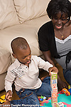 2 year old toddler boy with mother interaction playing with toys language development mother talking and involved  building with wooden blocks tower African American vertical