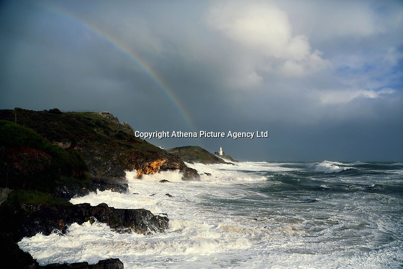 """Pictured: A rainbow appears in the sky as waves crash against Mumbles Lighhouse in Bracelet Bay, Swansea, UK. Monday 16 October 2017<br />Re: Remnants of Hurricane Ophelia are expected to bring strong gusts of wind to Wales when it hits Britain's shores.<br />The hurricane, making its way from the Azores in the Atlantic Ocean, will have weakened to a storm when it arrives.<br />A Met Office amber """"be prepared"""" warning has been issued in some areas bringing """"potential danger to life""""."""