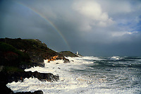 Pictured: A rainbow appears in the sky as waves crash against Mumbles Lighhouse in Bracelet Bay, Swansea, UK. Monday 16 October 2017<br />