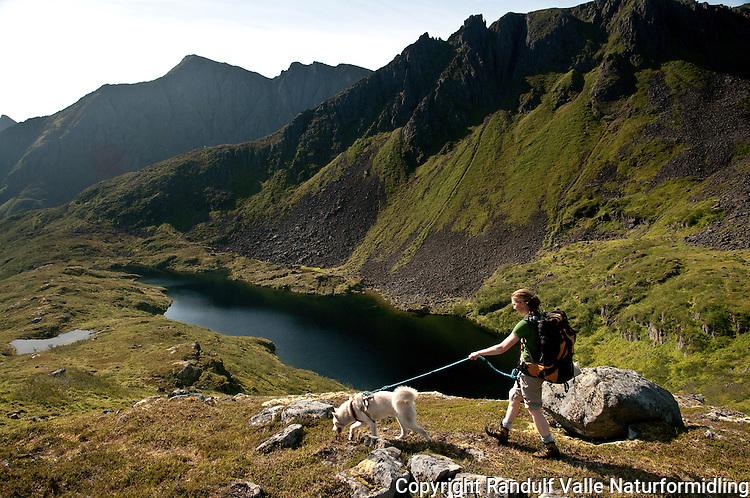 Dame og hund på vei ned Polldalen på Sørøya. ---- Woman hiking with dog.