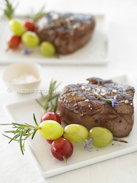 Beef steaks served with skewered red and green grapes, rosemary