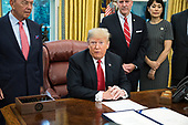 """United States President Donald J. Trump makes remarks prior to signing S. 3508, the """"Save Our Seas Act of 2018"""" in the Oval Office of the White House in Washington, DC on Thursday, October 11, 2018.  Pictured behind the President from left to right: US Secretary of Commerce Wilbur L. Ross, Jr.; US Senator Dan Sullivan (Republican of Alaska); and Julie Fate, wife of Senator Sullivan.<br /> Credit: Ron Sachs / CNP"""