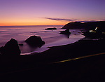 Cape Sebastian State Park Southern Oregon Coast Highway 101 at sunset looking north from viewpoint above coastline with rock formations and beach with car streaks Oregon State USA