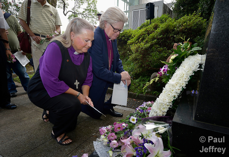United Methodist Bishop Mary Ann Swenson from the United States and Church of Norway Bishop Tor Berger Jorgensen pray after depositing flowers on a memorial marker during a ceremony in Nagasaki, Japan, on August 9, 2015, commemorating the 70th anniversary of the killing of Korean forced laborers when the United States dropped an atomic bomb on the city. The Koreans had been brought to Japan to work as slaves during the war. The church in Japan has played a key role in addressing Japan's complicity in violence and murder during the war years. The ceremony included the participation of Swenson and Berger Jorgensen and other members of a delegation of pilgrims from the World Council of Churches who each came to Japan to see for themselves the results of the bombings 70 years ago, to listen to survivors and local church leaders, and to recommit themselves to new forms of advocacy for a world free of nuclear weapons.