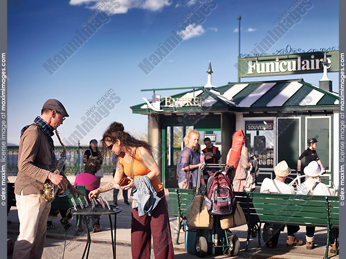 Woman tourist buying a CD of a street musician, saxophone player, by the funicular in old Quebec City, Quebec, Canada. Ville de Québec.