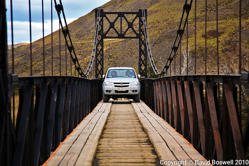 A narrow bridge is the way across the Paine River in Torres del Paine, Chile.