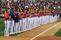 Members of the Clemson Tigers, including head coach Jack Leggett, left, stand for the National Anthem prior to a game against the South Carolina Gamecocks on Saturday, March 2, 2013, at Fluor Field at the West End in Greenville, South Carolina. Clemson won the Reedy River Rivalry game 6-3. (Tom Priddy/Four Seam Images)