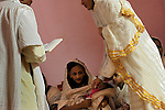 Eritrean asylum-seekers pray before conducting a baptism ceremony for two babies, at a side room of their makeshift church in southern Tel Aviv, Israel.