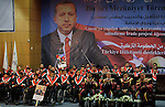 """A Palestinian man holds up a portrait of the Turkish Prime Minister Recep Tayyip Erdo?an, during the graduation ceremony of the first batch of the project titled """"Erada"""" in the Islamic University in Gaza city on Feb. 17, 2013. The project funded by the Turkish government aims to rehabilitation and training of Gaza war invalids and disabled. Photo by Ashraf Amra"""