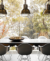 Three chrome pendant lights hang above the antique French table in the dining area