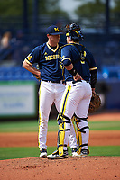 Michigan Wolverines starting pitcher Evan Hill (21) talks with catcher Harrison Wenson (7) during the second game of a doubleheader against the Canisius College Golden Griffins on February 20, 2016 at Tradition Field in St. Lucie, Florida.  Michigan defeated Canisius 3-0.  (Mike Janes/Four Seam Images)