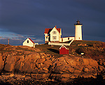 Cape Neddick - Nubble - Light Station (1879) in sunset light under dark clouds<br /> York County, ME