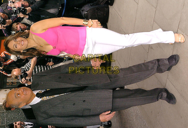 MOHAMED AL FYED &  ELIZABETH HURLEY.Arriving at Harrods for the launch of her new Beach line, Knighstbridge, London, April 12th 2004..full length pink top white trousers holding hands Liz.Ref: CAN.www.capitalpictures.com.sales@capitalpictures.com.©Can Nguyen/Capital Pictures