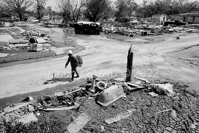 New Orleans, Louisiana.USA.September 28, 2005 ..At the exact point where the levy broke in New Orleans' lower 9th district Michael LaGarde, 33 years old, finds what remains of his home ... a mound of dirt and a few small items pushed aside by a massive barge that came through the levy when it broke...He was born and raised in this house and lived with his 3 children in the house before the hurricane and flood took it away. His grandparents built the house in 1940. It was 65 years old...One block behind his house is the house of his Aunt that was 2 stories high and survived the flood. After searching the house for photos and goods left behind he sits dazed in the streets of his old neighborhood that he has known all his life..