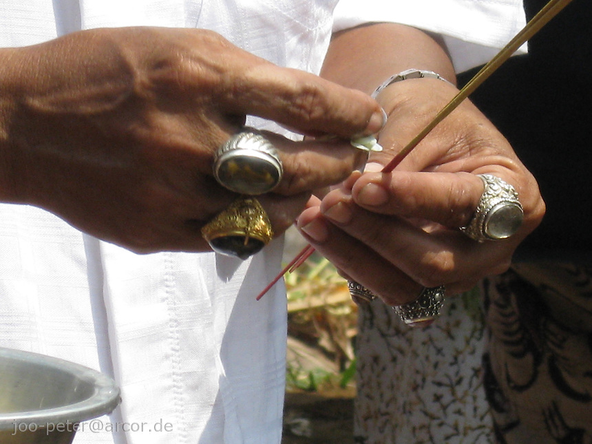 hands of a brahman with rings (believed to have magic powers), lightens candle sticks in cremation ceremonies in Tampak Siring, village of horn carving art, central Bali, archipelago Indonesia, August 2009