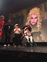 "Pictured: Seth Burke on stage speaking via video link to Dolly Parton<br /> Re: A brave schoolboy had his wish come true when he sang a duet with his favourite signing star Dolly Parton.  <br /> Seth Burke, nine, always listens to Queen of Country Dolly when he's in hospital having treatment for Duchenne's muscular dystrophy.<br /> Doting parents Lisa and John took him on a Caribbean cruise where the crew heard about his love for Dolly. <br /> The family was called up on stage one night and heard a familiar Tennessee drawl say: ""Hi Seth!""<br /> The schoolboy couldn't believe his eyes when he turned to see Dolly on a huge TV screen.<br /> Seth, of Grangetown, Cardiff, was diagnosed with Duchenne Muscular Dystrophy when he was a baby."