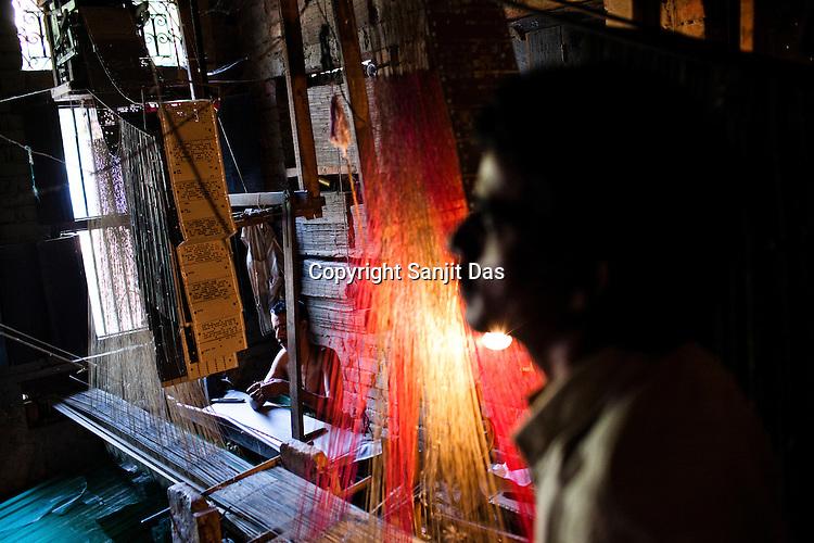 Md. Parvez, (left) one of the few muslim weavers using traditional looms to weave famous Benaresi saris in his workspace in Gazi Sadullahpura Bade Bazaar in Varanasi in Uttar Pradesh, India. Photograph: Sanjit Das/Panos