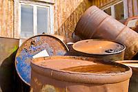 Rusting marine fuel barrels behind building, Steine, Lofoten, Norway