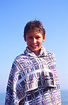 AMFY4C Young boy wrapped in towel after swimming against blue sky