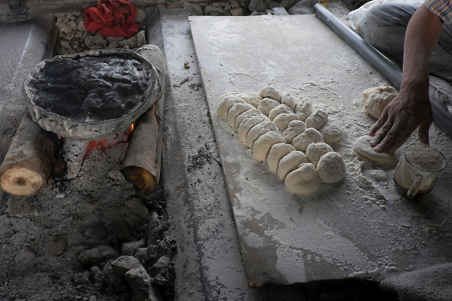 Makmoud Nakarch prepares the dough into small ball before rolling out the dough and cooking it on a flat plan over a wood fire. PHOTO BY JODI HILTON/PULITZER CENTER