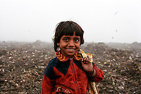 7 year old Jasmine stands among the refuse where she works on the Kajla rubbish dump.  It is one of three landfill sites in this city of twelve million people.  Around 5,000 tonnes of garbage are dumped here each day and over a thousand people work among the rubbish, sorting through the waste and collecting items to sell to retailers for recycling.