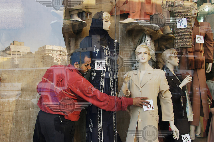 Adjusting window display of fashion store downtown.