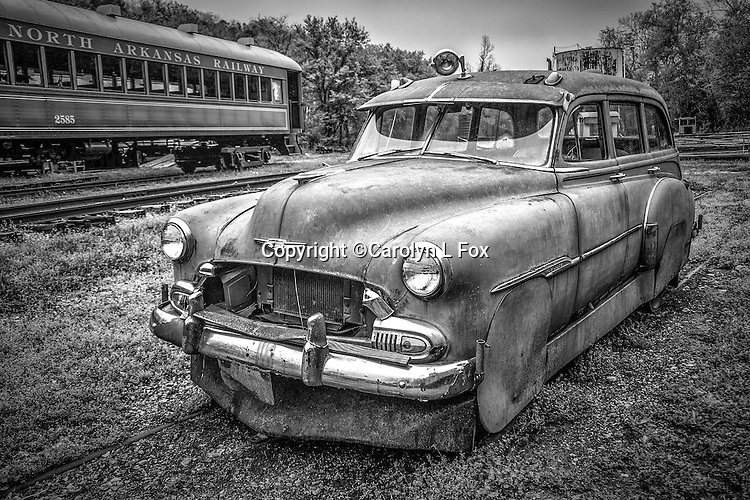 An old car sits next to a railroad track.