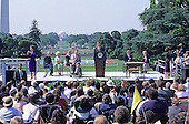 United States President George H. W. Bush signs the Americans with Disabilities Act of 1990 into law during a ceremony on the South Lawn of the White House in Washington, D.C. on July 26, 1990. Pictured, on stage, (left to right): unidentified interpreter, Reverend Harold Wilke, first lady Barbara Bush, U.S. Vice President Dan Quayle, Evan Kemp, President Bush, Justin Dart, Sandra Parrino, and unidentified interpreter.  The act prohibited employer discrimination on the basis of disability. <br /> Credit: Ron Sachs / CNP