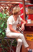 Woman age 22 sitting at outdoor sidewalk cafe bar.  Torun Poland