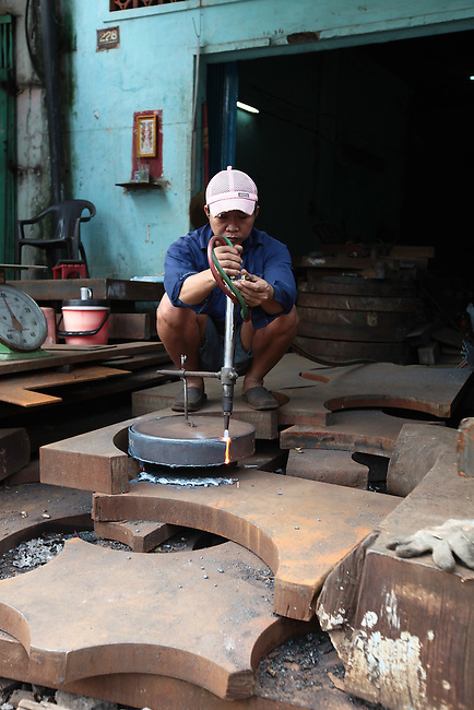 A man uses an acetylene torch to cut through a thick steel disk at a scrap metal shop in District 11 in Ho Chi Minh City, Vietnam. Aug. 16, 2011.